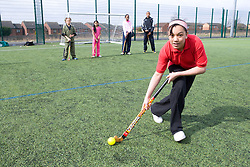 Group of children practicing hockey on a playing field at their local leisure centre,