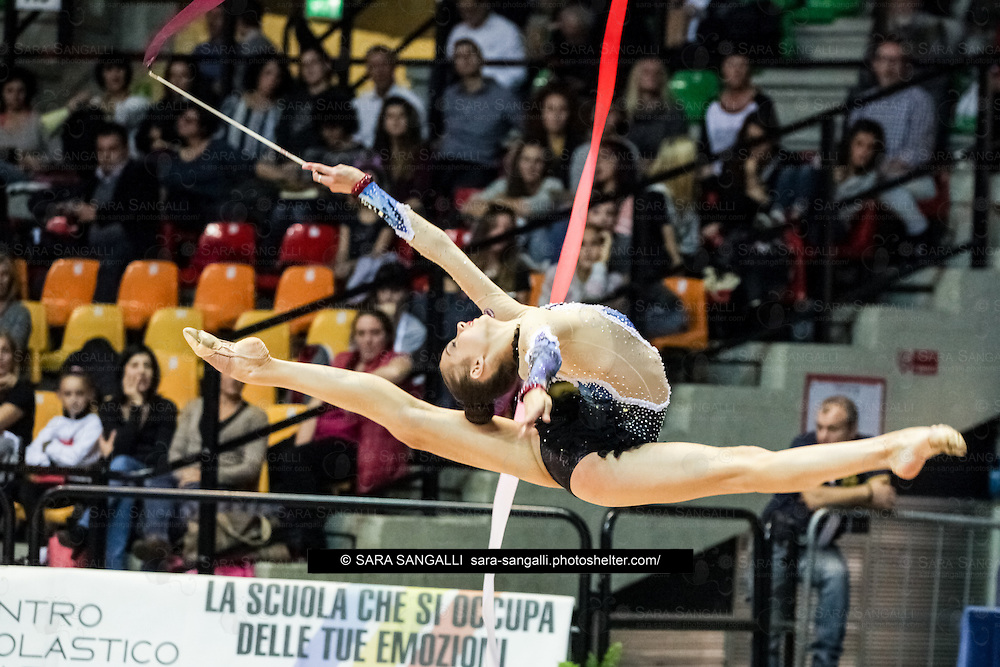 DESIO, ITALY - OCTOBER 31 2015: Eleonora Romanova of Ginnastica Terranuova performs with ribbon at the italian national rhythmic gymnastic championship. Her score in the apparatus is 17,000. Her team's score is 85,750 and ended up in third position.