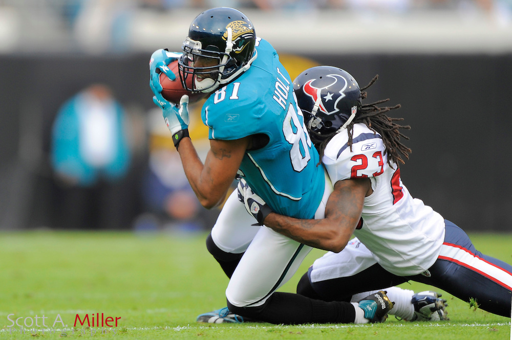 Dec. 6, 2009; Jacksonville, FL, USA; Jacksonville Jaguars wide receiver Torry Holt (81) is tackled by Houston Texans cornerback Dunta Robinson (23) during their game at Jacksonville Municipal Stadium. ©2009 Scott A. Miller