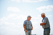 Farmers talking on a farm in Iowa.<br /> Photographed by editorial lifestyle Texas photographer Nathan Lindstrom