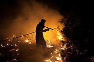 A volunteer firefighter works on a forest fire near El Cubillo de Uceda, on August 11, 2012 in Guadalajara, Spain. During a heat wave dozens of forest fires have appeared in Spain, three of them at National Parks, like Teide, Doñana or Cabañeros, and thousands of people had to be evacuated at La Gomera and Tenerife, in the Canary Islands.