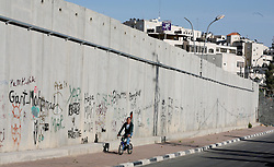 Jerusalem - May 4th,  2008 -- A teenager cycles along the wall in Jerusalem which separates Jerusalem and Ramallah, May 4th, 2008. Picture by Andrew Parsons / i-Images