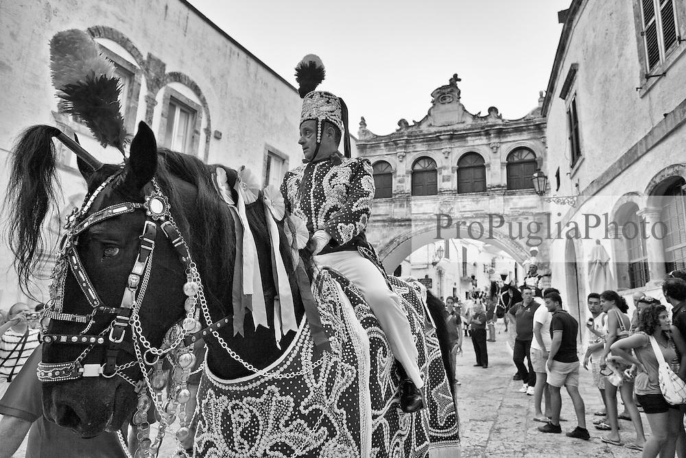 Ostuni Cavalcata S.Oronzo agosto 2012. Cavaliere a cavallo con lo sfondo dell'arco nella piazza della Cattedrale;.Sant'Oronzo si nascose anche in una grotta a Ostuni, nel luogo dove è stata poi costruita la chiesa e il relativo Santuario. I festeggiamenti si svolgono nella Città Bianca il 25, 26 e 27 agosto con la rinomata Cavalcata di Sant'Oronzo, una processione nella quale sfilano esponenti del clero e dell'amministrazione comunale, seguiti da cavalli e cavalieri, con stoffe rosse ricche di ricami e lustrini. I festeggiamenti comprendono anche due fiere e uno spettacolo di fuochi.