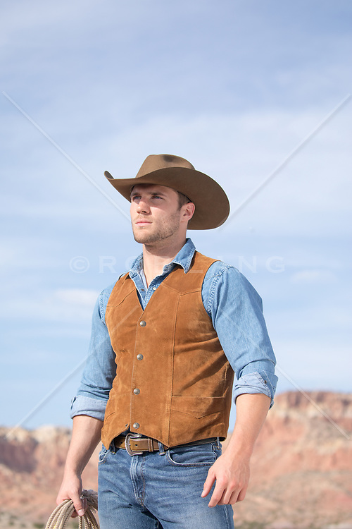 rugged cowboy outdoors overlooking a mountain range