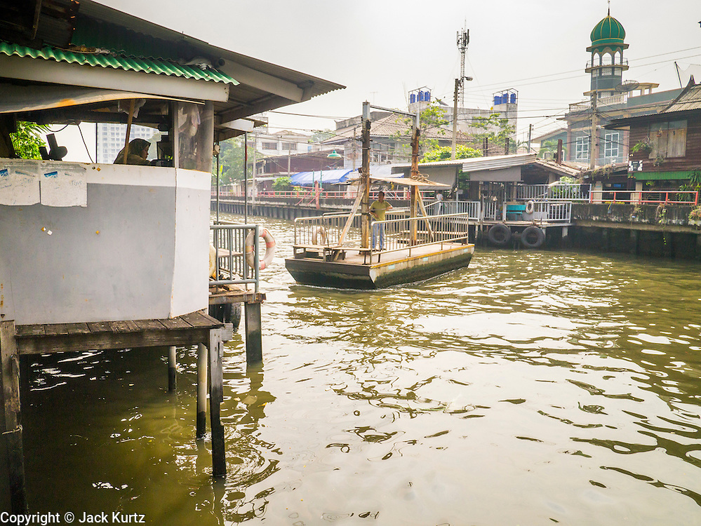 21 NOVEMBER 2012 - BANGKOK, THAILAND:  People cross Khlong Saen Saeb in Bangkok on a small ferry that is pulled across the Khlong by a pulley system. There are only a few ferries that cross the Khlong. They use a winch to pull the boat across the Khlong. The fare is 2 Thai Baht, about $0.10 (US). Bangkok used to be criss crossed by canals (called Khlongs in Thai) but most have been filled in and paved over. Khlong Saen Saeb is one of the few remaining khlongs in Bangkok with regular passenger boat service. Khlong Saen Saeb was dug in 1837 to be a military supply line from Bangkok to Siamese armies battling Annamese (now Vietnamese) forces in what is now Cambodia. Boats and ships play an important in daily life in Bangkok. Thousands of people commute to work daily on the Chao Phraya Express Boats and fast boats that ply Khlong Saen Saeb. Boats are used to haul commodities through the city to deep water ports for export.   PHOTO BY JACK KURTZ