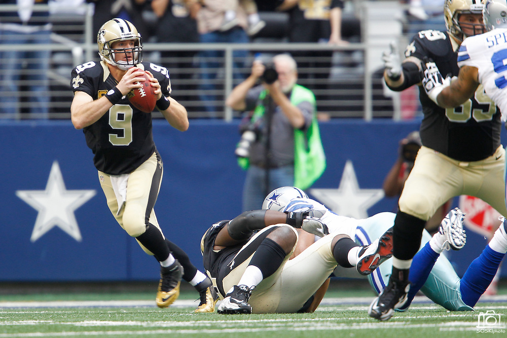 New Orleans Saints quarterback Drew Brees (9) looks for an open receiver as he scrambles from the Dallas Cowboys defense at Cowboys Stadium in Arlington, Texas, on December 23, 2012.  (Stan Olszewski/The Dallas Morning News)
