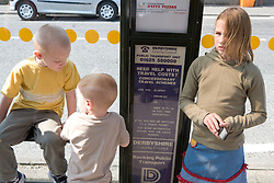 Sister waiting at a bus stop with her younger brothers,