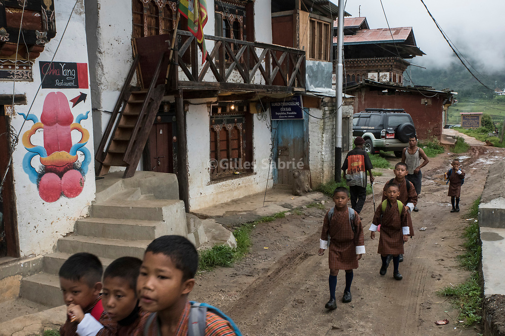 For a story by Steven Lee Myers, Bhutan<br /> Lobesa, Bhutan, August 2nd, 2017<br /> Boys on their way to school passing by a village house on which a phallus has been painted. Locals believe that the phallic symbols bring good luck and drives away evil spirits, Its origin can be found in the Bon religion that predated the advent of Tibetan Buddhism. Phallus representations are also linked to the XVIth century Lama Drukpa Kunley  popularly known as the &ldquo;Divine Madman&rdquo; for his unorthodox ways of teaching, and for his bizarre and shocking behaviours.<br /> Gilles Sabri&eacute; pour The New York Times