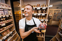 Cheerful salesman holding jar of jam in grocery store