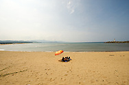 A lone sunbather relaxes under an umbrella on a beach in Fulong, Taiwan.