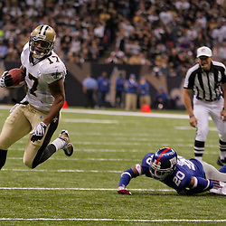 2009 October 18: New Orleans Saints wide receiver Robert Meachem (17) runs with the ball as New York Giants safety Michael Johnson (20) makes a diving attempt at a tackle during the second half at the Louisiana Superdome in New Orleans, Louisiana.