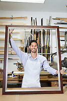 Portrait of a happy young craftsman holding big frame in workshop
