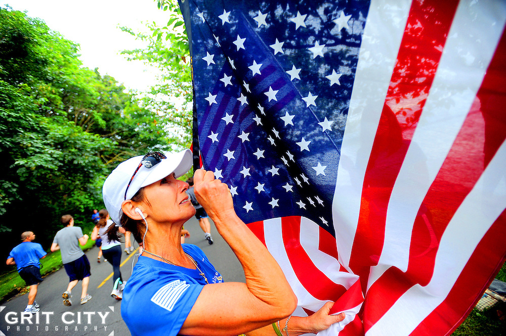 Photo by Ingrid Barrentine..Sybil Williamson, 56, touches the flag honoring her son, Sgt. Patrick Williamson, lining the route of the Rock 'N' Roll Seattle Marathon June 25, 2011.