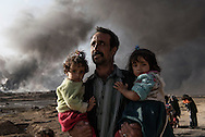 Iraq, Qarayya: A newly displaced man carries two children at a check point in Qayyara, south of Mosul on October 31, 2016. Alessio Romenzi