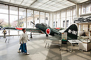 Tokyo, April 10 2014 - In the entrance of the Yushukan, Yasukuni's war museum, a monk walks in front of a A6M Zero fighter aircraft on display.