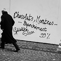 Banker passing graffiti left by 'les Indignés' (members of the Occupy movement) 'Chocolate, watches ... money laundering Swiss specialities', on a construction hoarding outside UBS at the entry to the Old Town.