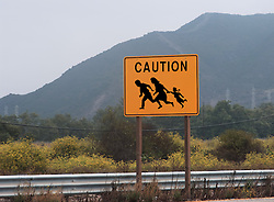 highway sign showing family crossing