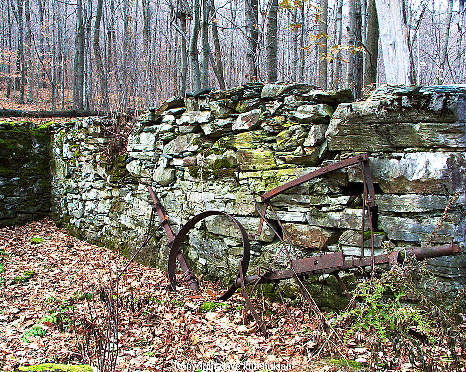 an abandoned stone foundation with an old piece of farm equipment against it. no property release