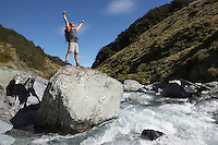 Hiker with arms outstretched on rock in river