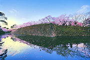 Sunrise at Hirosaki Castle Japan.A rare capture of the castle with a blue sky and the sun reflecting on the water of the moat. A few minutes earlier and the sky was dark, a few minutes later and the sky was washed out white.<br />