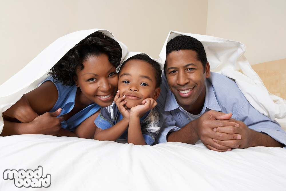 Family with son (3-6) lying underneath sheet portrait