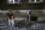 Coal delivery men shovel chunks of brown coal on a street in Aue, a mining town in the Ore Mountains known for its copper, titanium, and kaolinite. The town was a machine-building and cutlery manufacturing centre in the East German era with a population of roughly 18,000 inhabitants. It was the administrative seat of the former district of Aue-Schwarzenberg in Saxony and part of the Erzgebirgskreis since August 2008..