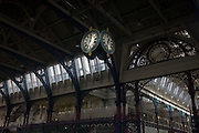 Ironwork and clock hanging from the roof of Smithfield meat and poultry market in Clerkenwell, London. Smithfield Market, a Grade II listed-covered market building, was designed by Victorian architect Sir Horace Jones, completed in November 1868 at a cost of £993,816 (£80 million at 2015 prices).