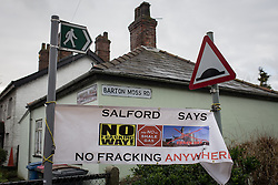 "© Licensed to London News Pictures . 26/01/2014 . Salford , UK . A banner reading "" Salford says no fracking anywhere "" suspended between signposts at the entrance to the approach road to the fracking site , on Barton Moss Road . Approximately 500 protesters march to an iGas fracking exploration site at Barton Moss , Salford , today (Sunday 26th January 2014) . They walk along the A57 road , blocking traffic as they do . A long term protest camp has been established on an access road leading to the site and today (26th January) protesters from other areas of the country travelled to the site to join with other protesters against fracking . Photo credit : Joel Goodman/LNP"
