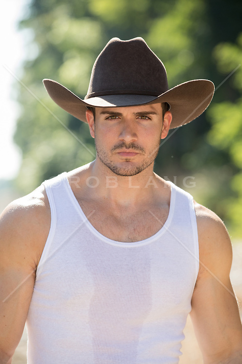 portrait of a rugged cowboy in a sleeveless tee shirt