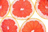 Closeup of sliced grapefruit on white background