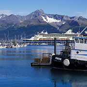 Fishing boats and Holland America Cruise ship SS Rhyndam in port with Kenai Mountains in back, Seward, Alaska
