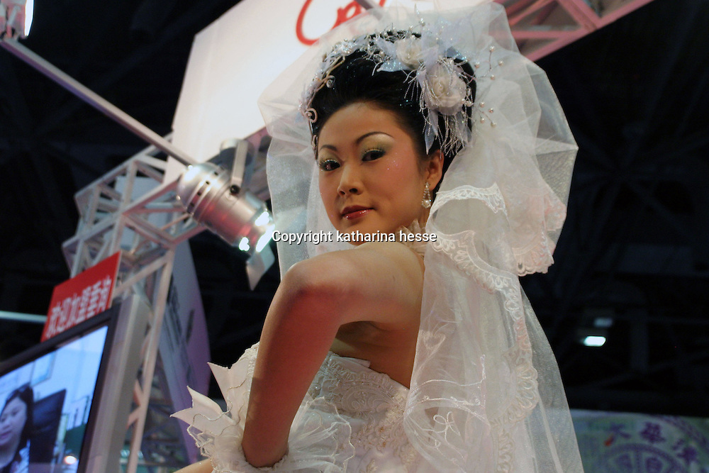 .. BEIJING, 22. October 2004 : a model shows Western-style bridal wear at the International Beauty Week in Beijing, October 22, 2004, in China. Beauty business is booming in China. Sales in beauty related businesses and products are worth more than 7 billion USD last year.      ..Whereas in Mao Zedong's China, even pigtails were seen as a sign of vanity (and had to be cut off) , nowadays, urban Chinese women seek about every means in order to distinguish themselves from the masses.  This year Beijing will organize the worl'd first beauty pageant for women who had plastic surgery in early December...