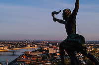 Budapest, Hungary.  Panorama view from Gellert Hill. Statue of torch bearer in foreground.