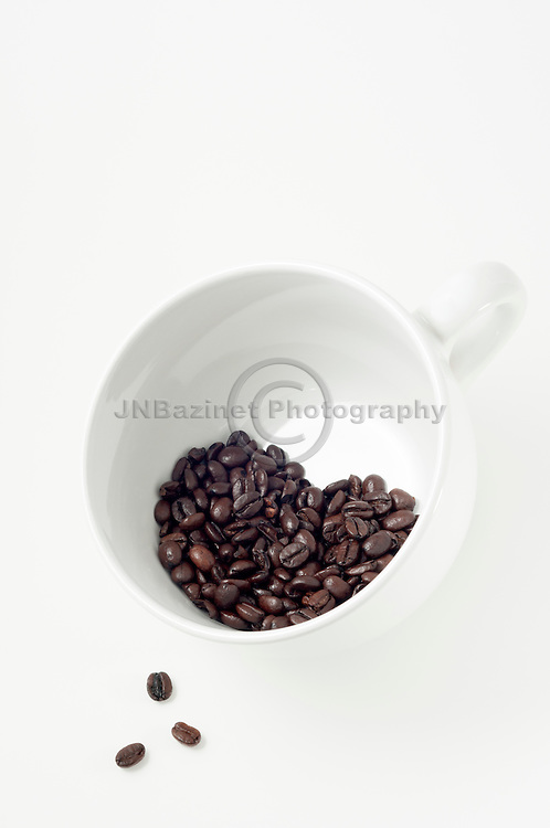 Three beans spill out of cup with heart shaped group of coffee beans.