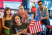 07 NOVEMBER 2012 - BANGKOK, THAILAND:   Members of Democrats Abroad watch Mitt Romney's concession speech at the Democrats Abroad election watch party in Bangkok. US President Barack Obama won a second term Tuesday when he defeated Republican Mitt Romney. Preliminary tallies gave the President more than 300 electoral votes, well over the 270 needed to win. The election in the United States was closely watched in Thailand, which historically has very close ties with the United States. The American Embassy in Bangkok sponsored an election watching event which drew thousands to a downtown Bangkok hotel. American Democrats in Bangkok had their own election watch party at a restaurant in Bangkok.     PHOTO BY JACK KURTZ