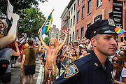 A man in an American Indian headdress and waving a rainbow flag waves to the crowd as a New York City police officer watches the crowd on Christopher Street near the Stonewall Inn.