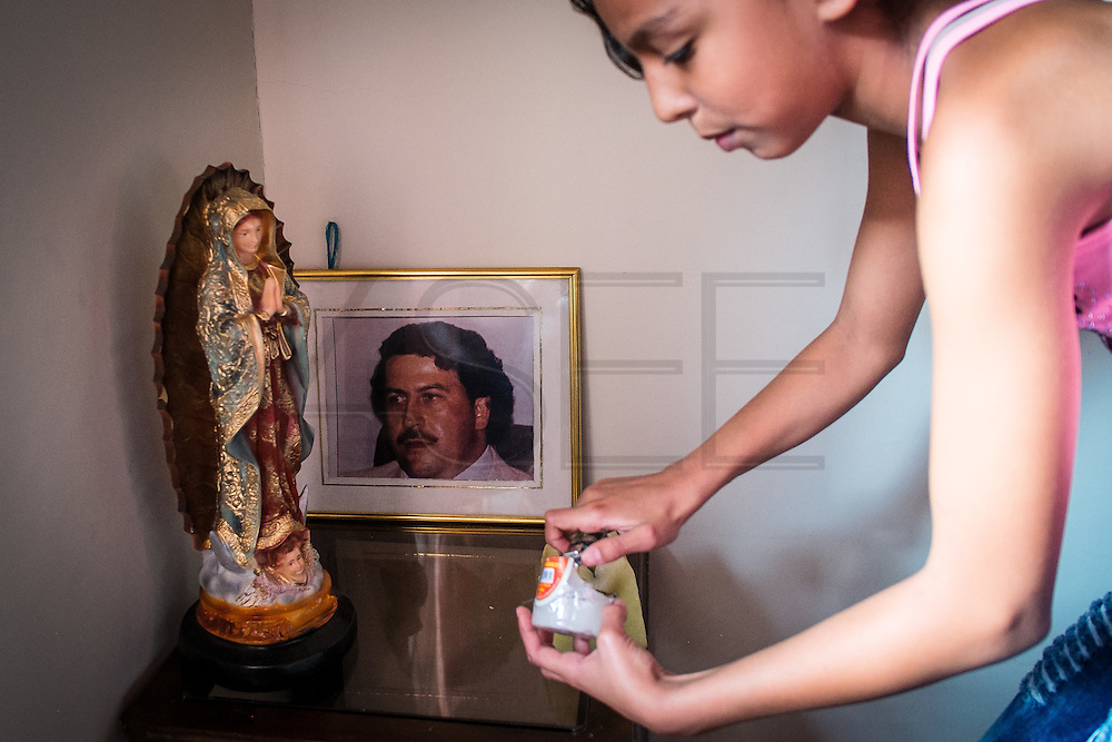 """2015/11/23 - Medellín, Colombia: Maria Miranda, 17,  lights a candle in the  altar in her father's house in honor of Pablo Escobar, Colombia's most famous drug lord. Habitants of the Escobar neighbour are forever grateful to Pablo Escobar. Originally called """"Medellin Sin Tugurios,"""" or Medellin Without Shanty Towns, Barrio Pablo Escobar is located high up on the eastern slope of Medellin, where Pablo Escobar built 413 houses, which he gave to poor people that used to live in a mountain of garbage in the Moravia neighbourhood. (Eduardo Leal)"""