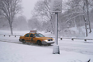 A yellow taxi in Central Park during a snowstorm<br /> New York City  U.S.A. Winter in New York