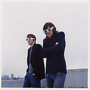 Two young men standing on rooftop wearing 3D glasses.