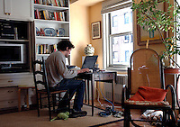 University Student studying at home oncomputer.