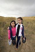 Best friends Vira Halim-Rotinsulu (left) and Isabel Durham, both nine years old, on a beach path at the Oregon Coast. (Fully released - 111106)