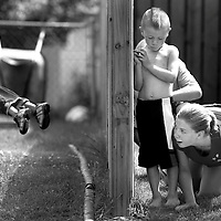 Jennifer Bergman, right, Brayden Prater, center and Rogan Mesteth hide behind a fence during a game of kick the tree. The game of kick the tree is a modern version of kick the can. Kade Prater, left took a break from the game to be spun around. The neighborhood children gathered at the Prater's house to enjoy the afternoon weather.