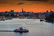 Djurgårdsfärjan på Stockholms Ström i skymning med röd himmel i Stockholm.
