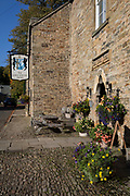 Exterior of the Lord Crewe Arms Hotel in the Northumbrian village of Blanchland on 29th September 2017, in Blanchland, Northumberland, England. Blanchland is a village in Northumberland, England, on the County Durham boundary. The population of the Civil Parish at the 2011 census was 135. Blanchland was formed out of the medieval Blanchland Abbey property by Nathaniel Crew, 3rd Baron Crew, the Bishop of Durham, 1674-1722. It is a conservation village, largely built of stone from the remains of the 12th-century Abbey. It features picturesque houses, set against a backdrop of deep woods and open moors. Set beside the river in a wooded section of the Derwent valley, Blanchland is an attractive small village in the North Pennines Area of Outstanding Natural Beauty.