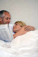 Couple looking in each others eyes lying in bed