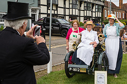 Datchet, UK. 30 June, 2019. Local residents dressed in period costume pose for photographs before the arrival of pre-1905 vehicles taking part in the 48-mile Ellis Journey from Micheldever station near Winchester to Datchet, a reenactment of the first recorded journey by a motorised carriage in England undertaken by pioneer automobilist Hon. Evelyn Ellis in his new, custom-built Panhard-Levassor on 5th July 1895. ​