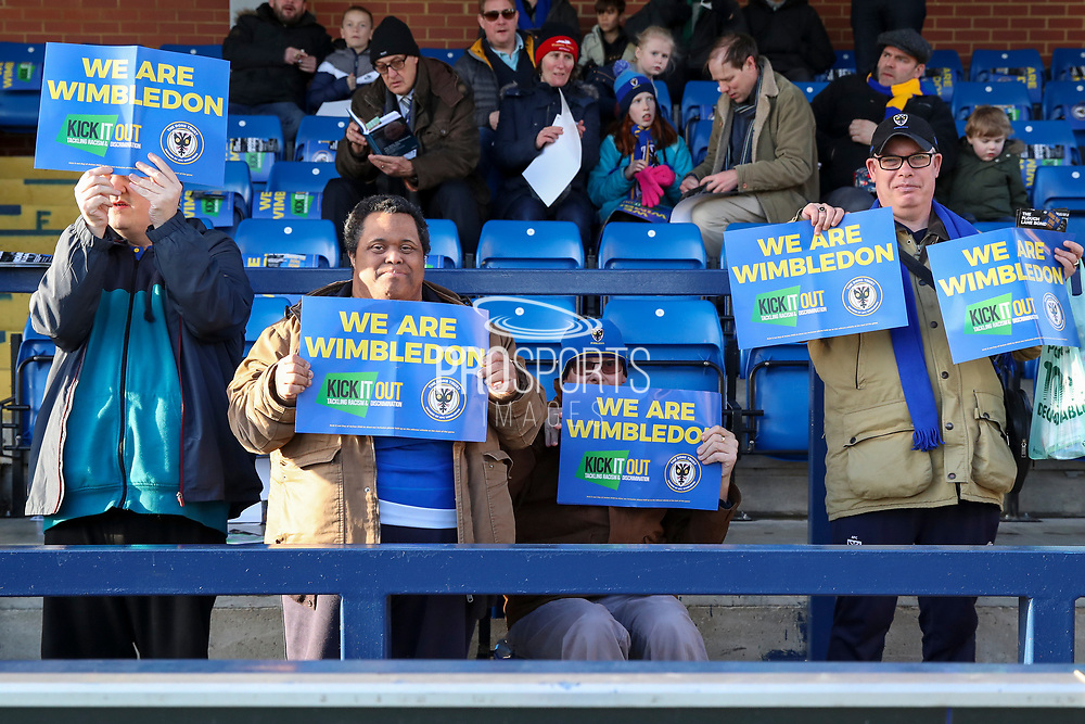 AFC Wimbledon fans with Kick it out signs during the EFL Sky Bet League 1 match between AFC Wimbledon and Peterborough United at the Cherry Red Records Stadium, Kingston, England on 18 January 2020.