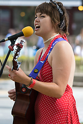 "London, July 18th 2015. Up and coming singer/songwriter Emily Lee perfoms a mixture of covers and self-penned songs from her recently released EP ""Don't Forget To Love"" in Leicester Square as part of the Busk in London Festival aimed at showcasing the outstanding talents of many of the capital's finest street performers, including, musicians, magicians, living statues, jugglers and bands."