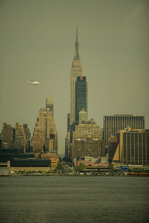 A view of the Empire State Building and the New Yorker hotel with an helicopter passing by.