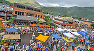 Despite a strong rain shower, crowds pack the 300 block of East Hopkins Avenue during the annual Mac 'N' Cheese Festival in Aspen, Colorado.